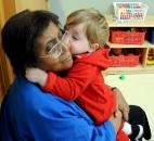 Carter Haas, 18 months, give his classroom foster grandmother, Idella Williams, a kiss during class Jan. 11 at Children's Village Early Learning Center, a part of Lutheran Social Services of Indiana, 6613 South Anthony Blvd.