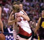 As the ball drops, Bishop Luers players Amy Frieburger and Jessica Hathaway hug after beating the Gibson Southern 51-37 for the Knights' fourth consecutive state championship. The Knights won this state title in their first year of moving up one class to Class 3A. News-Sentinel file photo