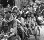 In this Jan. 28, 1974 file photo, Cambodians flee Khmer Rouge insurgents during artillery shelling of Phnom Penh. Still haunted by the Vietnam War next door and the 1970s genocide, the Southeast Asian country is not exactly the place that the world's refugees dream of reaching. Plagued by poverty, corruption and human rights abuses, it has been run by a strongman prime minister who has held power for 30 years. It's a nation where medical care outside main cities is nonexistent, where decent jobs