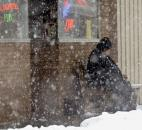 Despite the heavy snow a patron of O'Sullivan's on Main Street was sitting out front Sunday afternoon.(Photo by Ellie Bogue of The News-Sentinel).