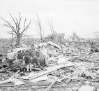 Searchers comb storm path: This scene, taken in the Shore community west of LaGrange early April 12, 1965, was typical as informal rescue teams searched for storm victims and valuables in the path of the Palm Sunday tornado that killed at least 19 people and injured 70 or more in western LaGrange County. In the background is rubble of the Shore Mennonite Church destroyed by the storm. At the moment the picture was taken, the searchers were looking for money reported left in the home.