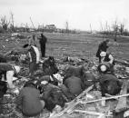 Assessing the damage: Workers begin sifting through the rubble at an unrecorded location after deadly tornadoes struck northeast Indiana on Palm Sunday 1965.