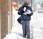 In downtown Fort Wayne streets were nearly empty as most residents stayed home. Scott Stockert, a postal worker, was making his way through snow drifts on North Wells Street on his rounds. Stockert said he was barely keeping warm. (Photo by Ellie Bogue of The News-Sentinel).