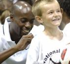 Fort Wayne, Ind. - DaMarcus Beasley, left, signs his autograph on the shirt worn by 5-year old Andrew Fender during a break in Beasley's National Soccer School summer camp on Wednesday at The Plex.. .Photo by Chad Ryan. Click for high resolution image.