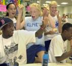 DaMarcus Beasley, seated at left, and his brother Jamar, seated at right, watch a replay of DaMarcus on video from a national game on July 6. Young fans Alyssa Ables, left, Ellie Sommer, center, and Gina Killion applaud his play.