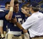 Bishop Dwenger head coach, Chris Svarczkopf, comforts  Bishop Dwenger quarterback Mike Fiacable at the end of the game.