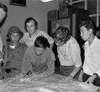 In this April 30, 1975 photo, the last three staffers in The Associated Press' Saigon bureau, reporters Matt Franjola, left, Peter Arnett, rear, and George Esper, second from right, are joined by two North Vietnamese soldiers and a member of the Viet Cong on the day the government of South Vietnam surrendered. One of the soldiers is showing Esper the route of his final advance into the city. More than two bitter decades of war in Vietnam ended with the last days of April 1975. Today, 40 years la