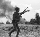 In this April 10, 1975 file photo, a South Vietnamese soldier gestures to a buddy as he runs along Route 4 in Tan An, South Vietnam during a battle, as a gas storage tank hit by Communist shells burns. (AP Photo/Lien)