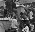 In this April 29, 1975 file photo, people try to scale the 14-foot wall of the U.S. embassy in Saigon, trying to reach evacuation helicopters, as the last of the Americans depart from Vietnam. (AP Photo/Neal Ulevich, File)