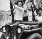 In this May 4, 1975 file photo, a youth waves a weapon and a Provisional Revolutionary Government (PRG) flag as he joins PRG troops on a jeep on Tu Do street in Saigon. (AP Photo/Matt Franjola, File)