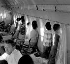 "In this April 1975 file photo, orphans aboard the first ""Operation Babylift"" flight at the end of the Vietnam War look through the windows of World Airways DC-8 jet as it flies them to the United States. (AP Photo/File)"