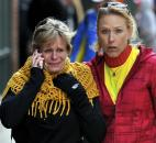 Women react as they walk from the area where there was an explosion during the Boston Marathon. Photo by By The Associated Press