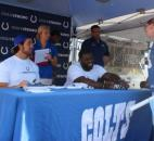 Offensive tackle Anthony Castonzo and guard Donald Thomas signed posters and T-shirts for fans Friday. Nicole Wilson of Fort Wayne was first in line to meet the players at the Colts Fan Fest at the Fort Wayne Newspapers Three Rivers Festival. (Photo by Jaclyn Goldsborough of The News-Sentinel)