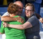 "Tom Sullivan, center, embraces family members as they look for his son, Alex Sullivan, who had gone to see ""The Dark Knight"" at the theater in Aurora, Colo., where a gunman opened fire. James Holmes is accused of killing 12 people and wounding dozens more in his July rampage. Photo by The Associated Press"