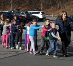 Connecticut State Police lead a line of children from the Sandy Hook Elementary School in Newtown, Conn., on Dec. 14. A gunman opened fire at the elementary school, killing 20 children and six adults before turning the gun on himself. It was one of the worst mass killings in the nation's history. Photo by The Associated Press