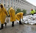 As rain from Hurricane Sandy arrives in Washington on Monday, workers haul sandbags to shore up vulnerable spots at The Pavilion at the Old Post Office. The Justice Department is seen in the background.