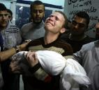 Jihad Masharawi weeps while he holds the body of his 11-month old son Ahmad after an Israeli air strike on their family house in Gaza City. The Israeli military and Hamas battled for eight days in November, leading to numerous civilian casualties. Photo by The Associated Press
