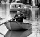 Using a board as a paddle, a Fort Wayne resident floats through the Nebraska neighborhood.