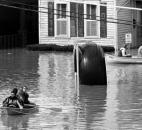 Residents boat down West Superior Street past car repair shop Fox & Fox's famous giant tire, center, which would later have the high-water line painted on it. The tire was eventually moved to a stand adjacent to the automotive shop, and a high-water marker took its place.