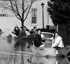 Residents leave their flooded Nebraska neighborhood homes on March 14, 1982. This view is from the West Main Street bridge looking west. Being resourceful, the people in the second boat are using snow shovels as paddles.
