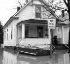 A boat is tied to the front porch of a flooded house in the West Main Street area.
