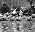 Boys rest atop a wall of sandbags.