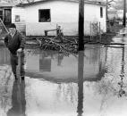 George Brinkman, of 4017 Elm St., one of the first residents back in the area, works to clear a drain. Soon after the photo was taken, Brinkman succeeded and the water disappeared down the sewer.