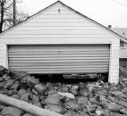 Sandbags from the Pemberton dike engulf a garage. Sandbaggers widened the base of the sandbag wall into the yard in order to stop the water that was seeping under the dike.