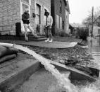 Residents watch water from their homes being pumped out into the street as the floodwaters subside.