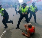Police officers react to a second explosion at the finish line of the Boston Marathon in Boston. Photo by By The Associated Press