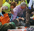 Medical workers aid injured people at the 2013 Boston Marathon after an explosion in Boston. Photo by By The Associated Press