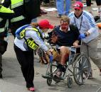 Medical workers aid an injured man at the 2013 Boston Marathon after an explosion in Boston. Photo by By The Associated Press