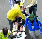 Medical workers aid an injured man at the finish line of the 2013 Boston Marathon after an explosion in Boston. Photo by By The Associated Press