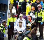 Medical workers aid injured people at the finish line of the 2013 Boston Marathon after an explosion in Boston. Photo by By The Associated Press