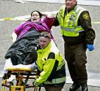 Medical workers aid an injured woman at the finish line of the 2013 Boston Marathon after two explosions Monday. Photo by By The Associated Press