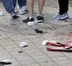 Blood from victims covers the sidewalk on Boylston Street at the site of an explosion during the 2013 Boston Marathon in Boston. At the right foreground is a folding chair with the design of an American flag on the cover. Photo by By The Associated Press