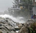 Viewers react as waves crash against a seawall near homes in Scituate, Mass., on Monday.