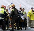 Two Boston Marathon volunteers hug each other, at right, as an injured person is loaded into an ambulance in the aftermath of two blasts near the finish line of the Boston Marathon in Boston. Photo by By The Associated Press