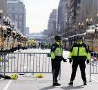 Boston police officers stand on Boylston Street near empty buses meant to transport runners who were instead diverted from the course after an explosion at the finish line Monday. Photo by By The Associated Press