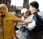 An unidentified Boston Marathon runner, center, is reunited with loved ones near Copley Square after an explosion in Boston. Photo by By The Associated Press