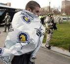Boston Marathon runner Russell Clifford of Marlborough, Mass., walks past SWAT officers near the finish line of the Boston Marathon in Boston on Monday. Photo by By The Associated Press