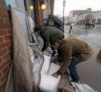 Omar Said, right, and Robert Stewart, center, place sandbags in front of Mills Fine Wine and Spirits in downtown Annapolis, Md., on Monday as Hurricane Sandy bears down on the region.