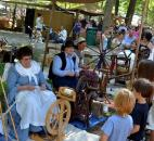Weather was good for this year's Johnny Appleseed Festival in September, drawing large crowds. Here a group of children watch and talk with settlers spinning yarn. Photo by Sarah Janssen