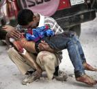 A Syrian man cries while holding the body of his son killed by the Syrian Army in Aleppo, Syria, this October. The country was wracked by civil war throughout the year, with no end in sight, as rebels tried to topple President Bashar Assad. Photo by The Associated Press