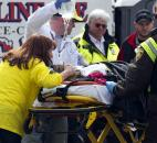 Emergency responders comfort a woman on a stretcher who was injured in a bomb blast near the finish line of the Boston Marathon on Monday. Photo by By The Associated Press