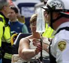 Emergency responders help a woman who was injured in a bomb blast near the finish line of the Boston Marathon on Monday. Photo by By The Associated Press