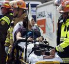 Emergency responders aid a woman on a stretcher who was injured in a bomb blast near the finish line of the Boston Marathon on Monday. Photo by By The Associated Press