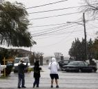 Residents look down a flooded street Monday as Hurricane Sandy approaches in Mastic Beach, N.Y.