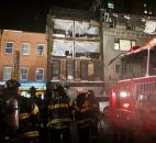 Firefighters respond at the scene where the facade of a four-story building on 14th Street and 8th Avenue collapsed onto the sidewalk Monday in New York.
