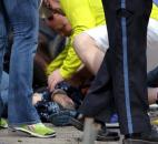 In this photo provided by The (Boston University) Daily Free Press and Kenshin Okubo, people help an injured person after an explosion at the 2013 Boston Marathon in Boston. Photo by By The Associated Press